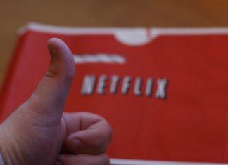 Una mano con el pulgar arriba delante de una hoja que se lee Netflix